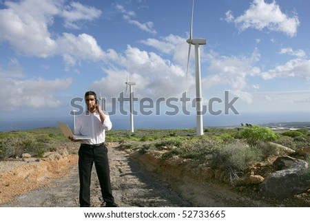 Businessman next to wind turbines with a laptop computer and a phone