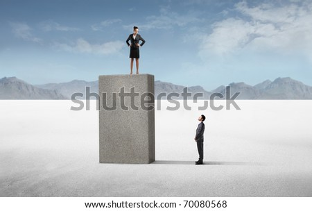 Businessman observing a businesswoman on a high cube - stock photo