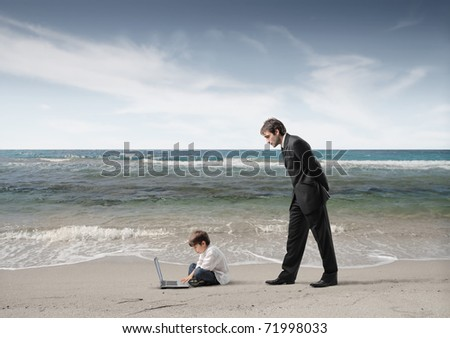 Businessman observing a child using a laptop - stock photo