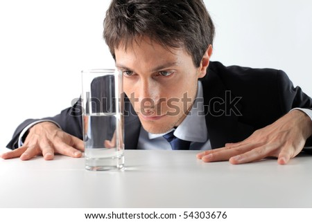 Businessman observing a half full glass of water - stock photo