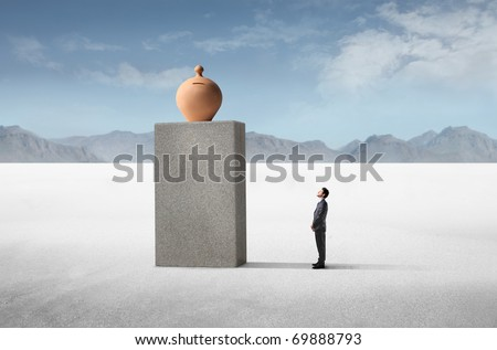 Businessman observing a money box on a high cube - stock photo