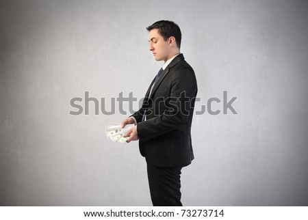Businessman observing some banknotes in his hands - stock photo