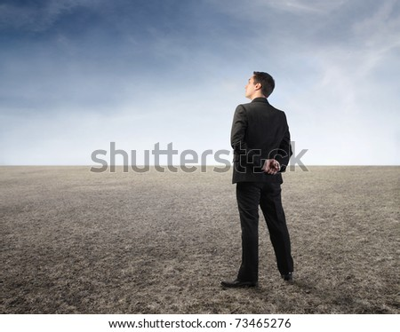 Businessman observing the desert in front of him - stock photo