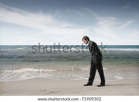 Businessman observing the sand at the seaside - stock photo