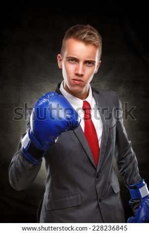 Businessman of 21 st century.  Young Businessman with boxing gloves  on dark background