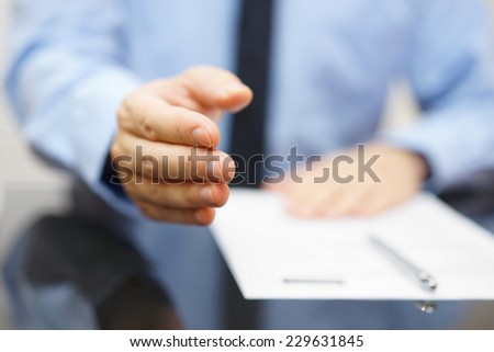 Businessman offering a handshake and contract - stock photo