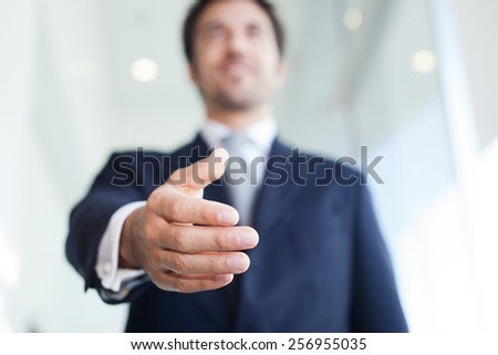 Businessman offering an handshake. Selective focus - stock photo