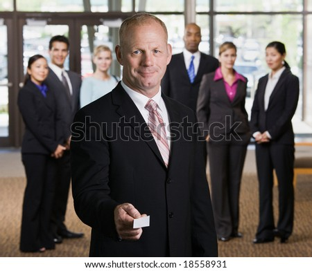 Businessman offering business card in front of co-workers - stock photo