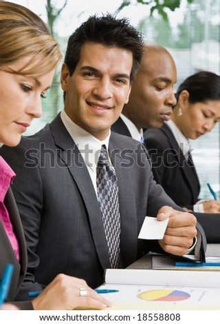 Businessman offering business card to female colleague - stock photo