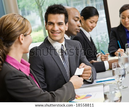 Businessman offering business card to female colleague in conference room - stock photo