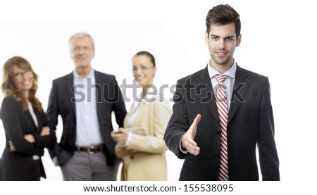 Businessman offering for handshake in office, his colleagues in the background, isolated on white. - stock photo