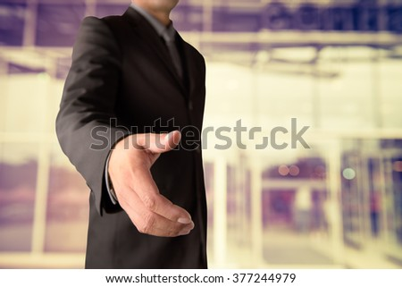 Businessman offering for handshake on office buildings blur background - stock photo