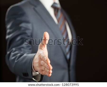 Businessman offering handshake to you on black background - stock photo