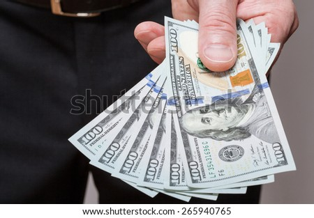 Businessman offering money to you - stock photo