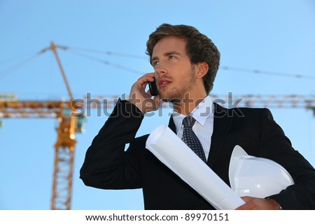 businessman on a construction site talking on his cell phone - stock photo
