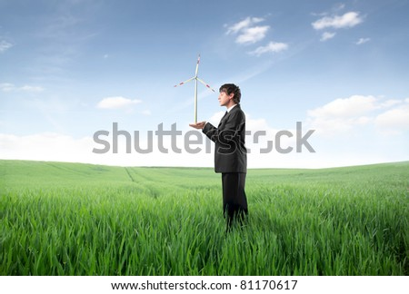 Businessman on a green meadow holding a wind turbine in his hands - stock photo