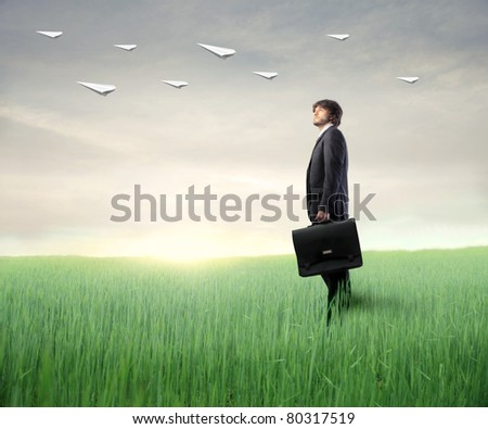 Businessman on a green meadow observing some paper airplanes - stock photo