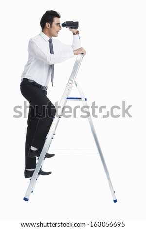 Businessman on a ladder and looking through binoculars