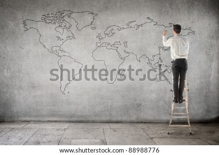 Businessman on a ladder drawing a world map - stock photo