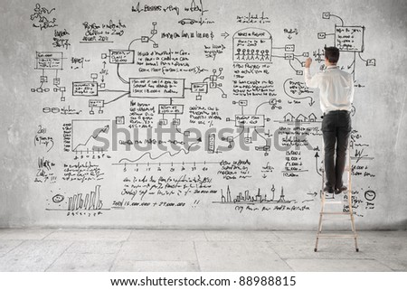 Businessman on a ladder writing some calculations - stock photo
