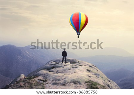 Businessman on a peak observing a hot-air balloon - stock photo