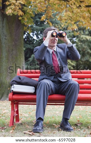 Businessman on a red park bench looking through binoculars - stock photo