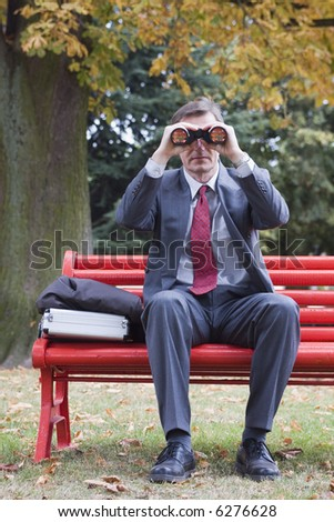 Businessman on a red park bench searching with binoculars - stock photo