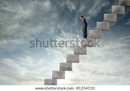 Businessman on a stairway looking downwards - stock photo
