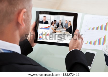 Businessman on a video or conference call on his tablet with an image of work colleagues in a meeting and bar graphs on the screen - stock photo