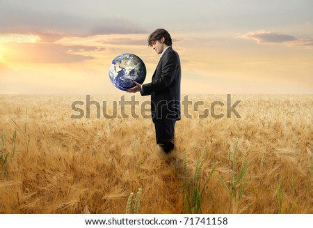 Businessman on a wheat field holding the Earth - stock photo