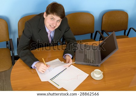 Businessman on a workplace with the laptop and a coffee cup - stock photo