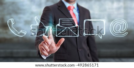 Businessman on blurred touching manuscript contact icon with his finger