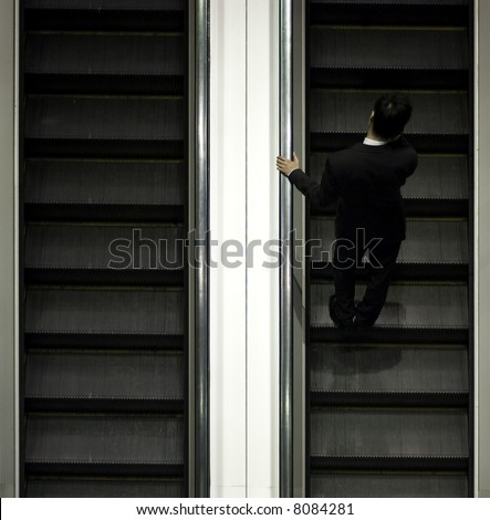 businessman on escalator with mobile - stock photo