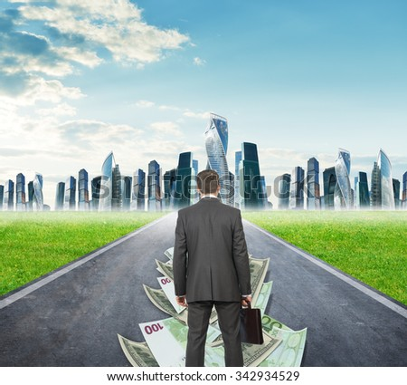 Businessman on money road going to city, rear view - stock photo