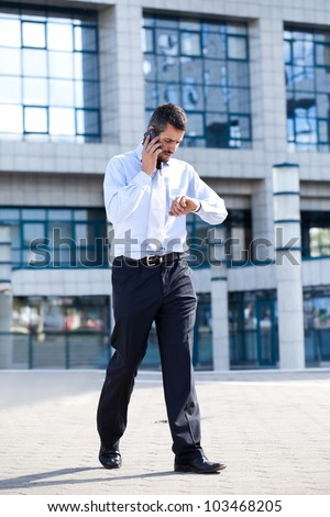 businessman on  phone and checking his watch in front of his office building, running late - stock photo