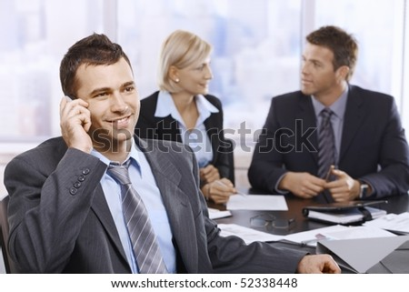 Businessman on phonecall in office meeting with colleagues sitting in background.
