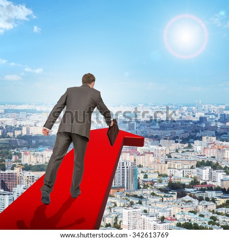 Businessman on red arrow above city, rear view - stock photo