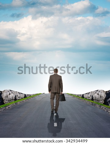 Businessman on road with mountains and blue sky, rear view - stock photo