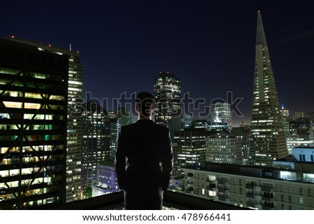 Businessman on rooftop looking at illuminated night city. Research concept