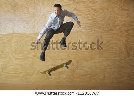 Businessman on skateboard in midair - stock photo