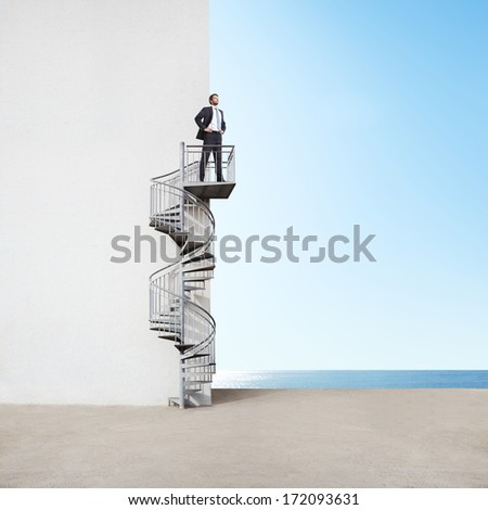 Businessman on spiral staircase - stock photo
