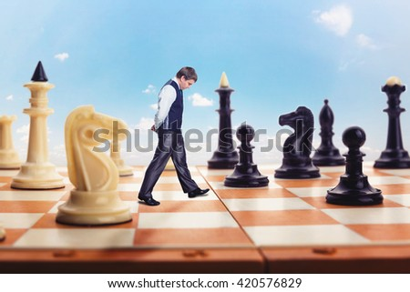 Businessman on the chess board - stock photo