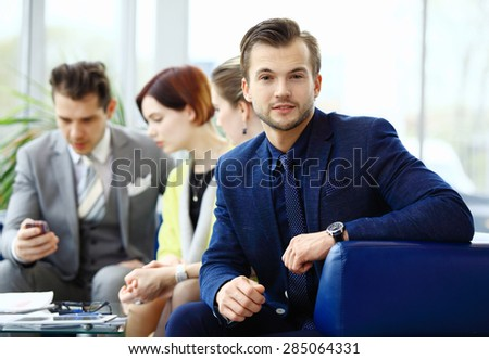 Businessman on the foreground and his coworkers discussing business - stock photo