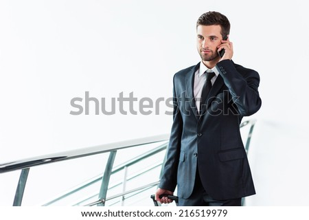 Businessman on the Go. Confident young businessman in suit talking on the mobile phone and carrying suitcase while walking away - stock photo