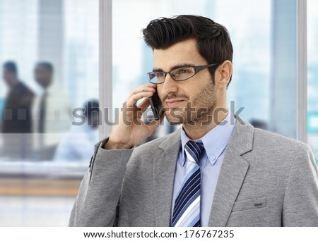 Businessman on the phone at office, looking away. - stock photo