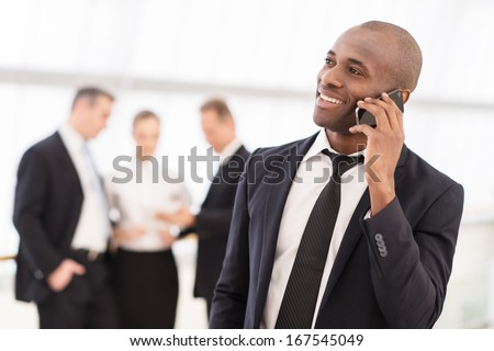 Businessman on the phone. Cheerful young African man in formalwear talking on the mobile phone and smiling while his colleagues standing on background - stock photo