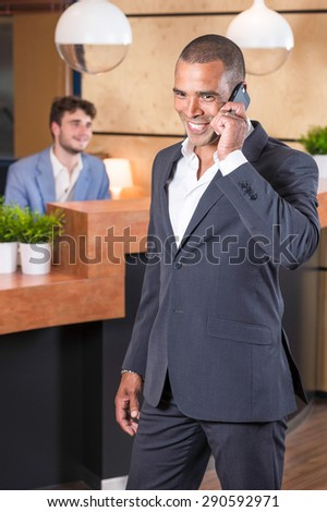 Businessman on the phone in the lobby of his office - stock photo