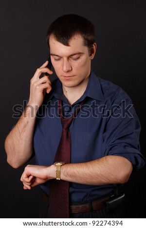 Businessman on the phone looking at his watch - stock photo