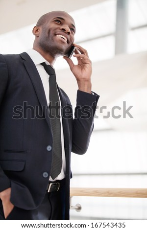 Businessman on the phone. Low angle view of cheerful young African man in formalwear talking on the mobile phone and smiling - stock photo