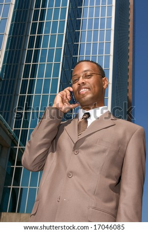 Businessman on the phone outdoors on background of reflective office building - stock photo